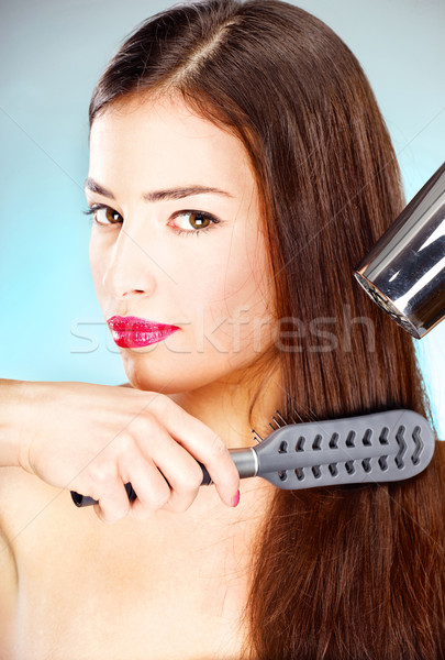 Stock photo: woman with long hair holding blow dryer and comb