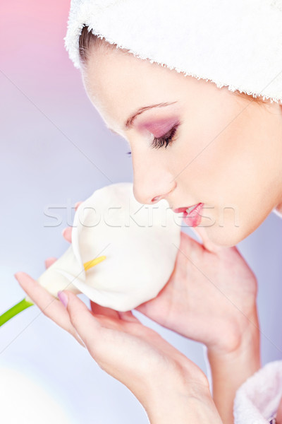 Stock photo: woman with towel on head holding flower
