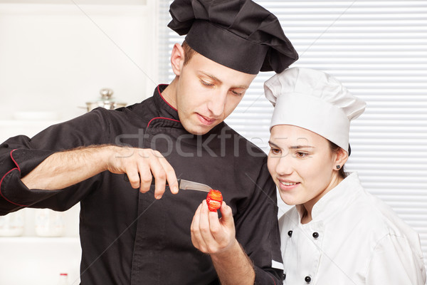 Senior chef teaches young chef to decorate fruit Stock photo © imarin