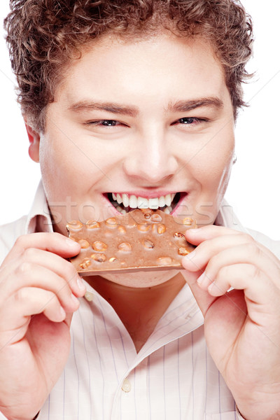 Happy chubby young man eating a slice of chocolate Stock photo © imarin