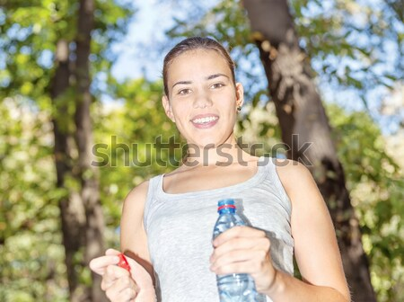Happy girl in forest holding bottle of water Stock photo © imarin