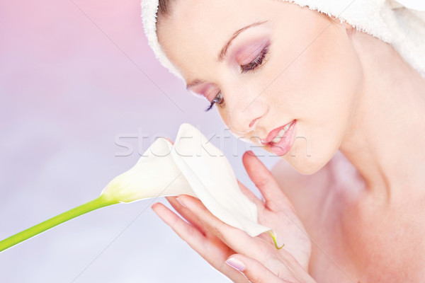 pretty woman with towel gently holding a white flower Stock photo © imarin