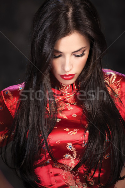 woman in red Cheongsam on dark background Stock photo © imarin