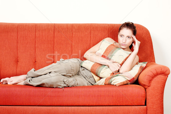 Woman with headache laying on sofa at home Stock photo © imarin