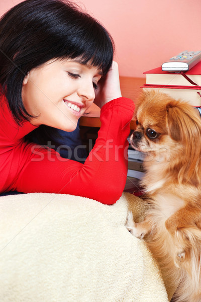Stock photo: Smiled girl at home with her Pekingese dog