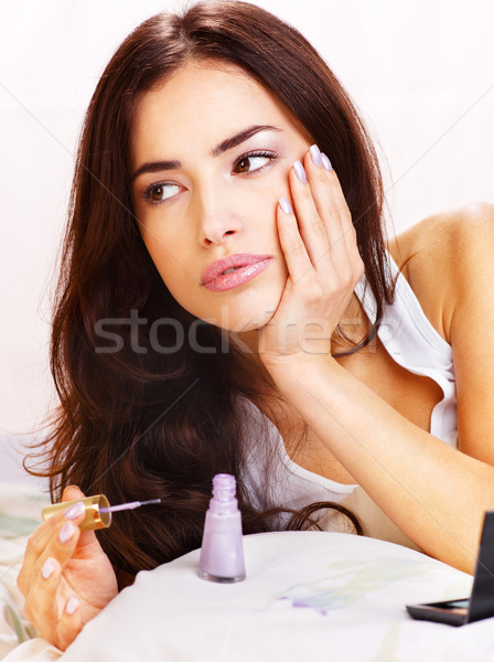 Stock photo: woman in bed applying nail polish