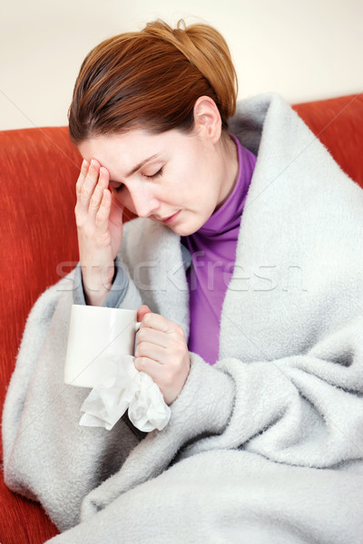 sick woman with a cup of tea in her hand Stock photo © imarin