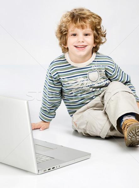 Blue curl hair boy seating near laptop Stock photo © imarin