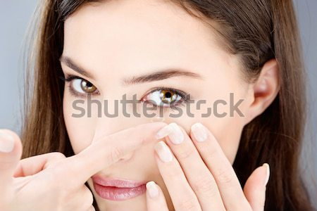 woman putting contact lens Stock photo © imarin
