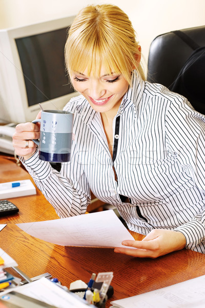 Stock photo: blond businesswoman checking the papers in office