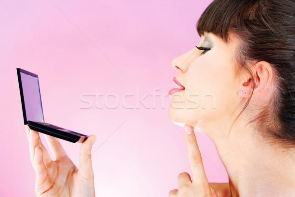 woman checking face skin in mirror Stock photo © imarin