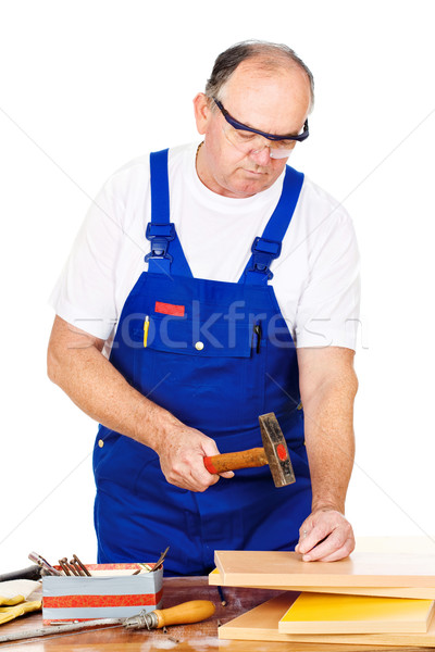 Middle age worker hammering nails in board Stock photo © imarin
