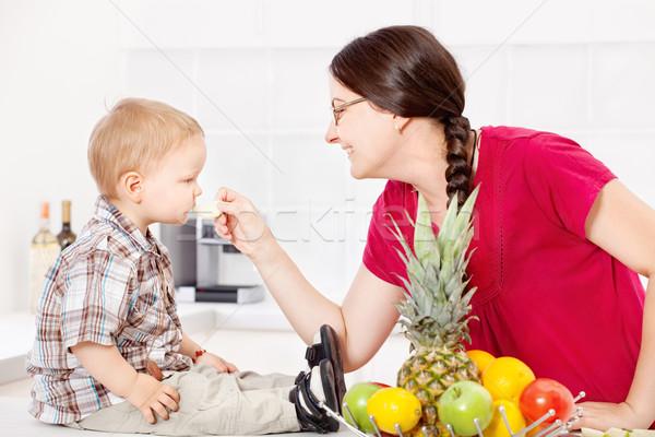 Mother feeding child in kitchen Stock photo © imarin