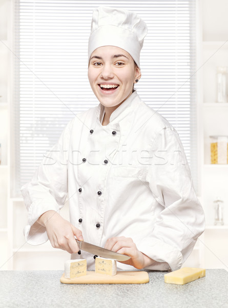 young chef cutting blue cheese in kitchenn Stock photo © imarin