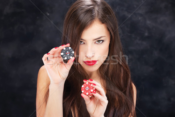 Stock photo: woman holding chips for gambling