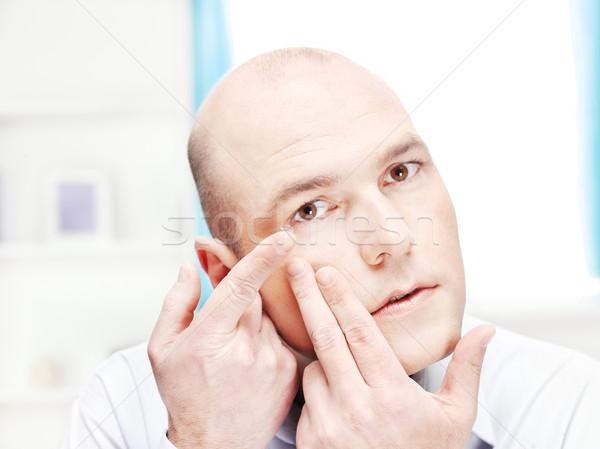 man putting contact lens in his eye Stock photo © imarin