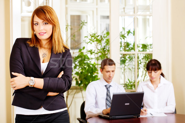 Handsome female manager with employers in office Stock photo © imarin
