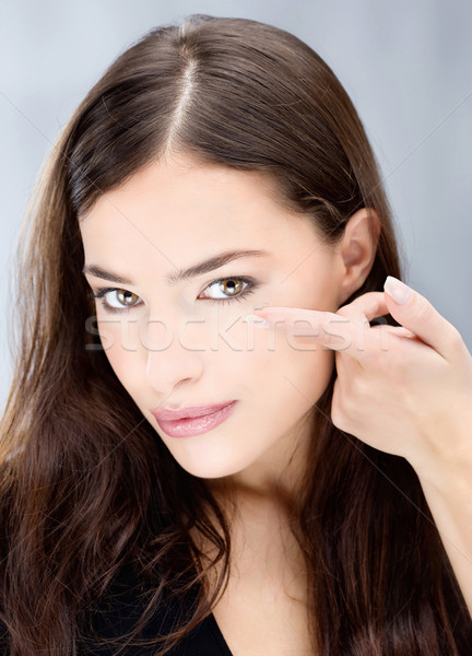 Stock photo: Woman hold conctact lens in front of eye