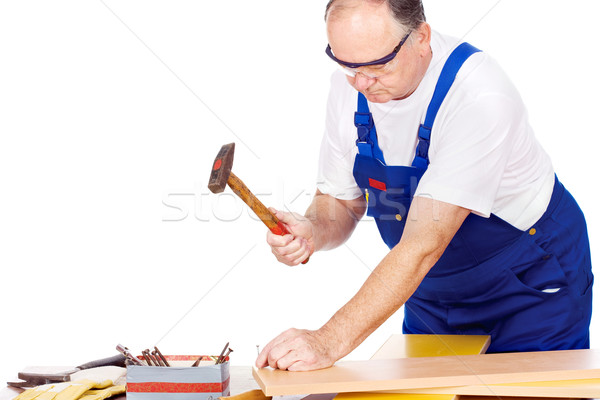 Middle age worker knocking the nail in board Stock photo © imarin