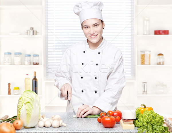 Stock photo: Young chef cutting onions in kitchen