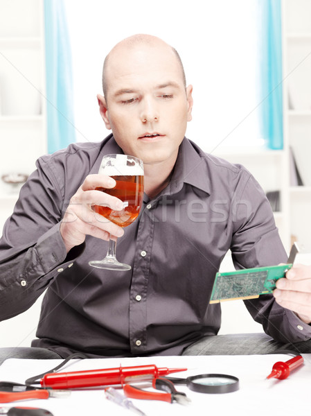 man with beer doing minor electronic repair at home Stock photo © imarin