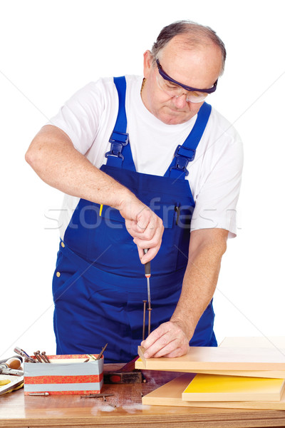 Stock photo: Middle age worker screwing nail in panel board