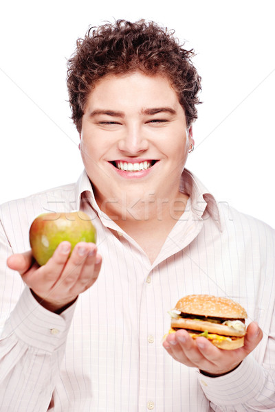Young chubby man holding apple and hamburger Stock photo © imarin