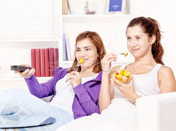 Tinilányok néz tv eszik gyümölcssaláta kanapé Stock fotó © imarin