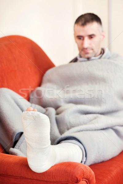 Férfi törött láb kanapé otthon medve fájdalom Stock fotó © imarin