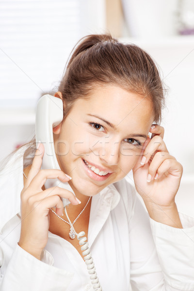 Stock photo: Woman on land line call, smiling at camera