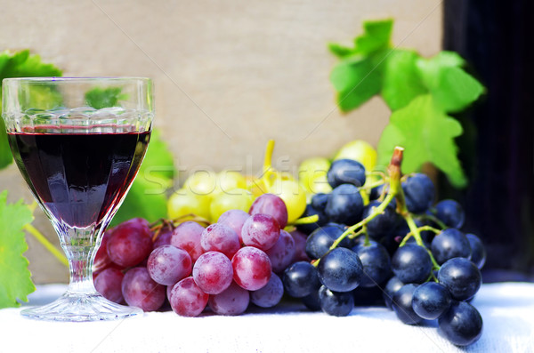 Stock photo: glass of red wine with grapes on a table