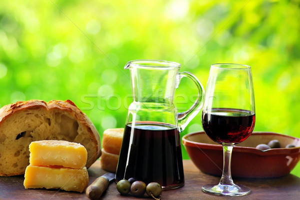 Stock photo: Red wine and food on table.