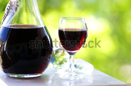 Stock photo: Glass of red wine on books.