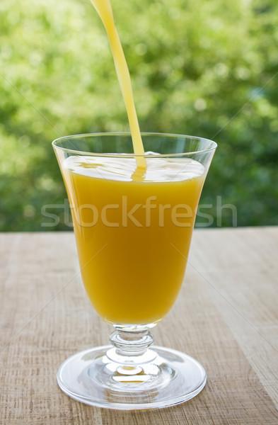 áramló friss narancslé üveg zöld levelek közelkép Stock fotó © IngridsI