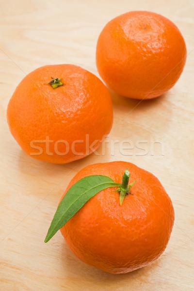 Drie rijp vers mandarijn vruchten groene bladeren Stockfoto © IngridsI