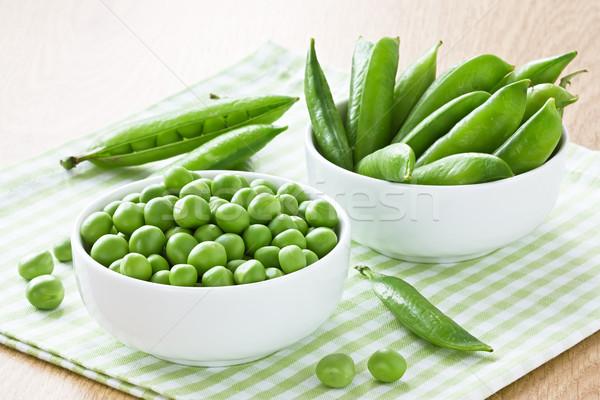 Zöld zöldborsó fehér tál fa asztal eszik Stock fotó © IngridsI