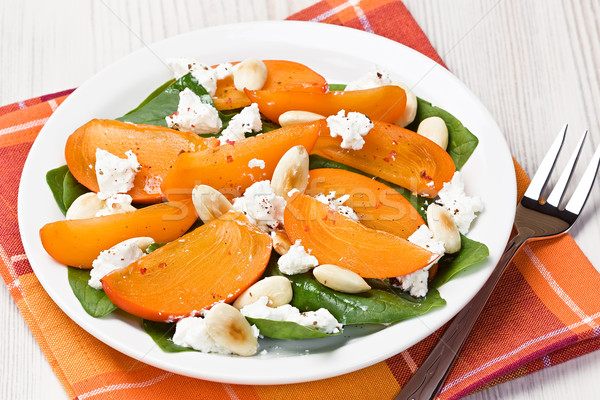 Stock photo: Spinach persimmon goat cheese salad