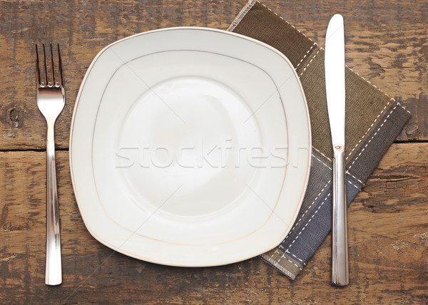 Empty dish, knife and fork and brown napkin on wood table  Stock photo © inxti