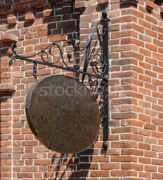 Blank, dark, shop sign hanging in a wrought iron bracket from a  Stock photo © inxti