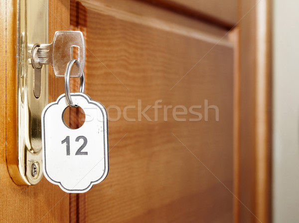Door handles on wood wing of door and key in keyhole with number Stock photo © inxti