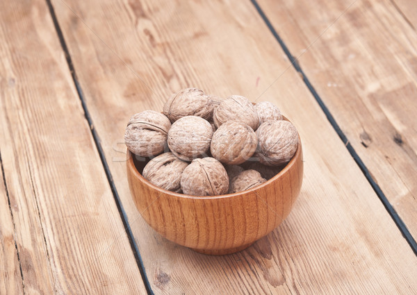 whole walnuts lying on faded wood with additional nuts in wooden Stock photo © inxti