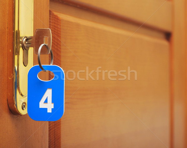 Door wood and key in keyhole with numbered label Stock photo © inxti