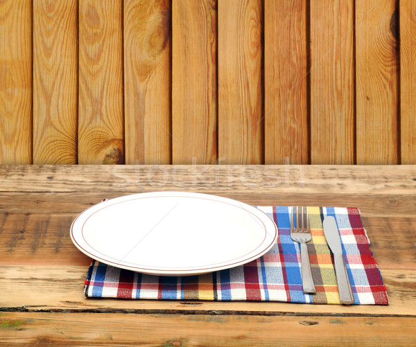 Empty white plate with fork and knife on wooden table Stock photo © inxti