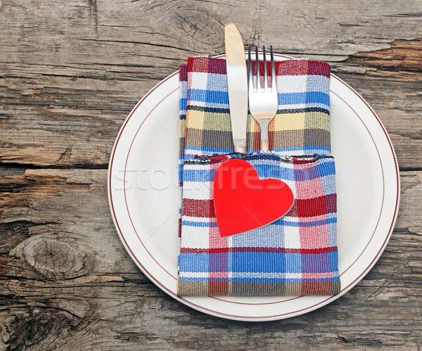Stock photo: Cutlery in the colorful napkin and red heart on an empty plate