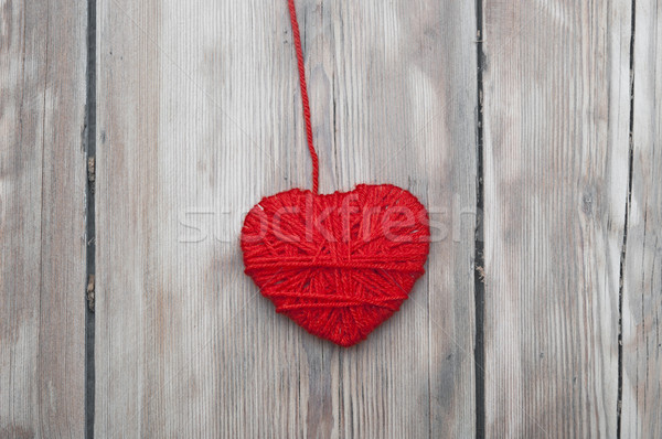 a heart made of red wool yarn hanging on old wood background.  Stock photo © inxti
