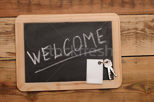 word 'welcome' and key on small school wooden blackboard Stock photo © inxti