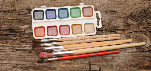 paints and brushes on wooden table  Stock photo © inxti