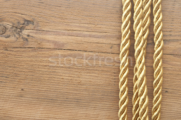 Twisted gold rope on wooden background  Stock photo © inxti