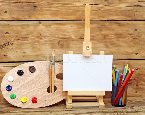 Stock photo: Wooden easel with clean paper and artistic equipment