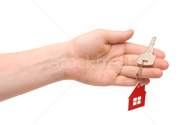 Hand holding key with a keychain in the shape of the house on th Stock photo © inxti